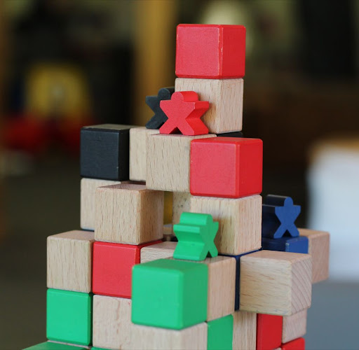 a stack of colored wooden cubes with little human-shaped wooden game pieces on top