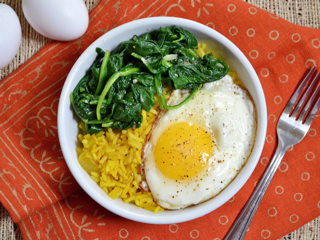 Golden Rice Bowls (rice topped with spinach and fried egg) with a fork on the side