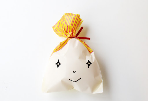 If you can't find plastic bags printed with a cute little face on them, why don't you try drawing your own cute faces onto plain plastic party bags? You could also use stickers or cut contact into shapes.