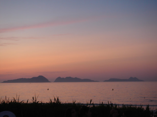 Galicia, Spain: from blue flags to green pastures. Sunset over the Cies Islands, Atlantic Ocean. Puesta del sol, Islas Cíes, Playa de Patos.