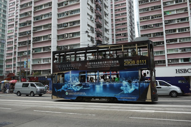Tram in Hong Kong with The Gloucester condos advertising