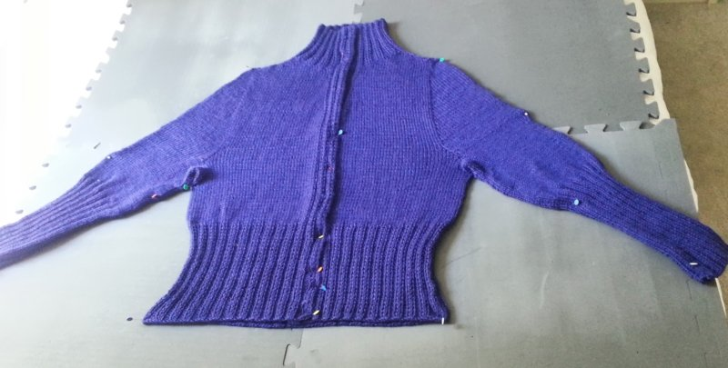 completed blue-violet hand knit cardigan pinned to a blocking board