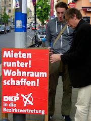 Zwei Genossen befestigen DKP-Plakat an Lichtmast. »Mieten runter! Wohnraum schaffen! DKP in die Bezirksvertretung«.