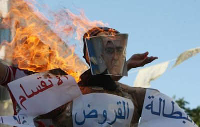 Palestinian protesters burn an effigy of prime minister Salam Fayyad during a demonstration against the high cost of living in the southern West Bank city of Hebron on 4 September 2012. Photo: AFP - Hazem Bader
