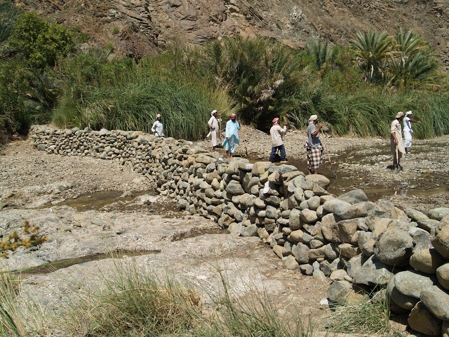 Workers shore up the dam at Wadi Jazira.