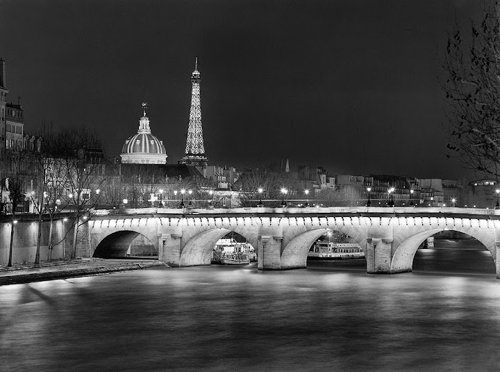 A view of the Pont Neuf from upstream with the Insitut de France and the Eiffel tower in the background. The Insitut de France is a learned society, grouping five académies, the most famous of which is the Académie française. From The Glow of Paris: The Bridges of Paris at Night. Photographer Gary Zuercher.