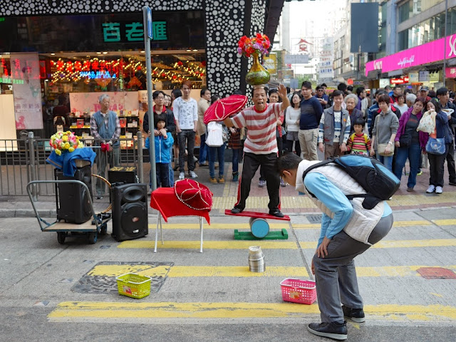 man balancing on a Rolla Bolla while also balancing a vase with flowers on his head at Sai Yeung Choi Street South