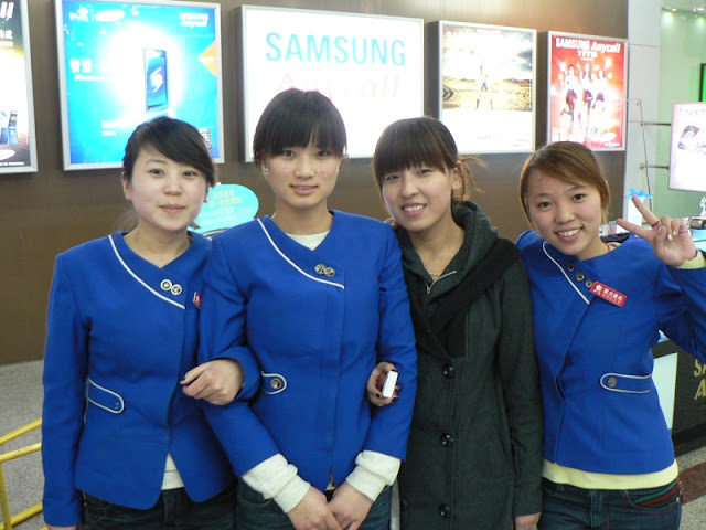 four young ladies at mobile phone store