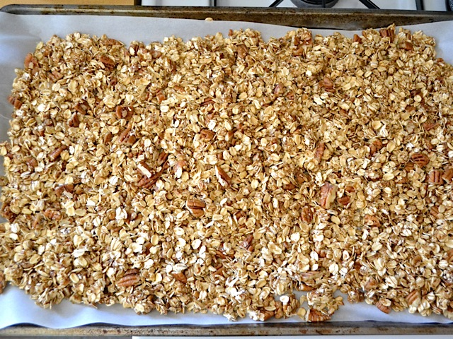 baking sheet covered in parchment paper with oats poured on top ready to bake