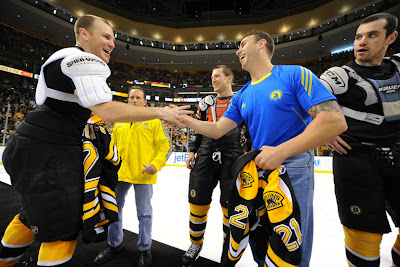 Shawn Thornton #22 of the Boston Bruins shakes hands with one of the first responders from the Boston Marathon tragedy after the game