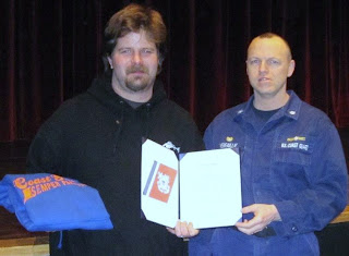 Clayton Paddock, a resident of Valdez and captain of the fishing vessel Windward, was awarded a certificate of merit by Cmdr. Darryl Verfaillie, commanding officer of Marine Safety Unit Valdez, March 1 for his efforts to rescue fellow fishermen in Prince William Sound August 2010. U.S. Coast Guard photo.