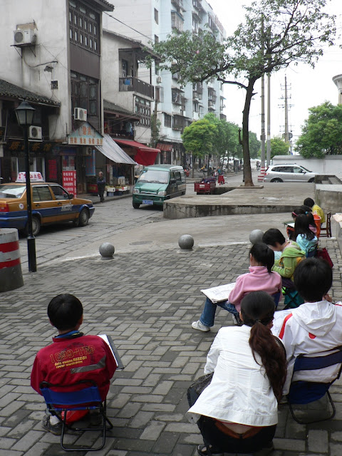 children sitting on a brick sidewalk drawing buildings in Changsha