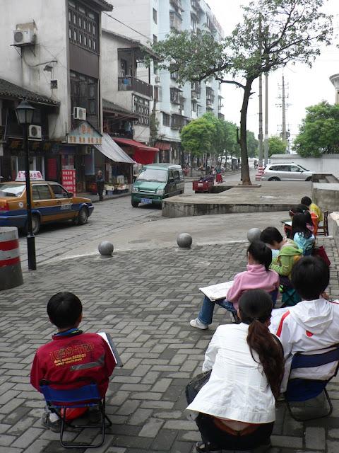 children sitting on a brick sidewalk drawing buildings in Changsha