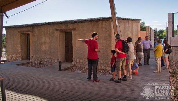 Antes de empezar la visita, junto al educador medioambiental en el exterior de la vivienda recreada.
