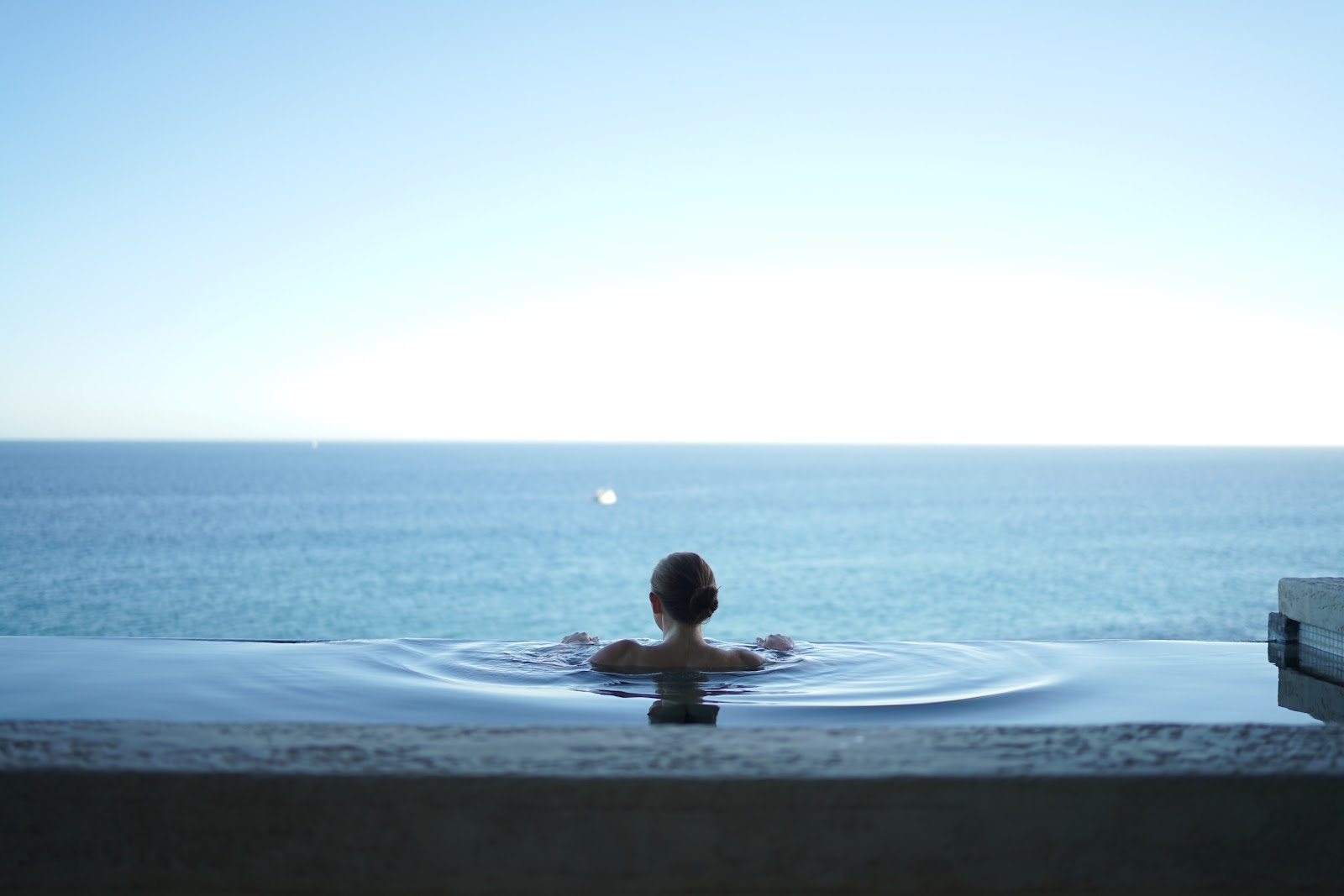 woman in infinity pool looking out to sea