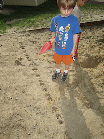 A child looks at a row of cone-shaped holes in a sandbox.