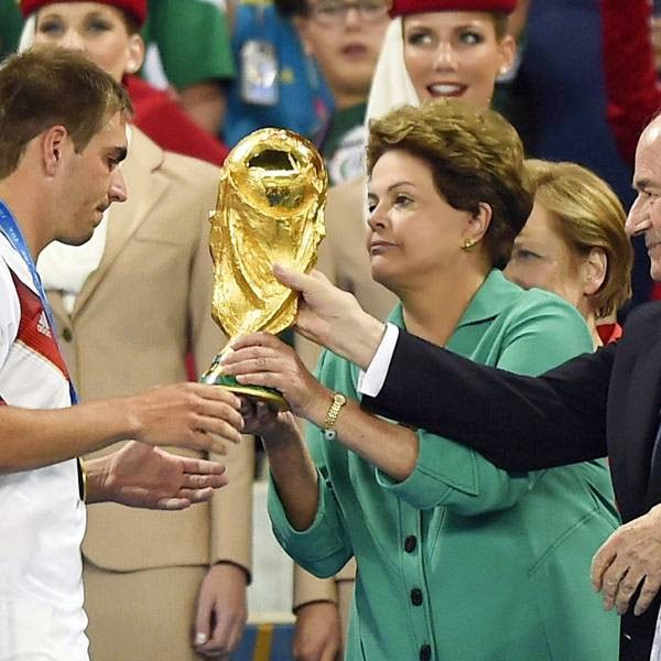 Germany's defender and captain Philipp Lahm (front L) is presented with the World Cup trophy by Joseph Blatter FIFA President (R) and Brazil's President Dilma Roussef after Germany won the 2014 FIFA World Cup final football match between Germany and Argentina 1-0 following extra-time at the Maracana Stadium in Rio de Janeiro, Brazil, on July 13, 2014.