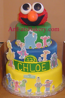 Unique three tier green, blue, and yellow fondant Kid's Sesame Street character cake with Elmo edible topper
