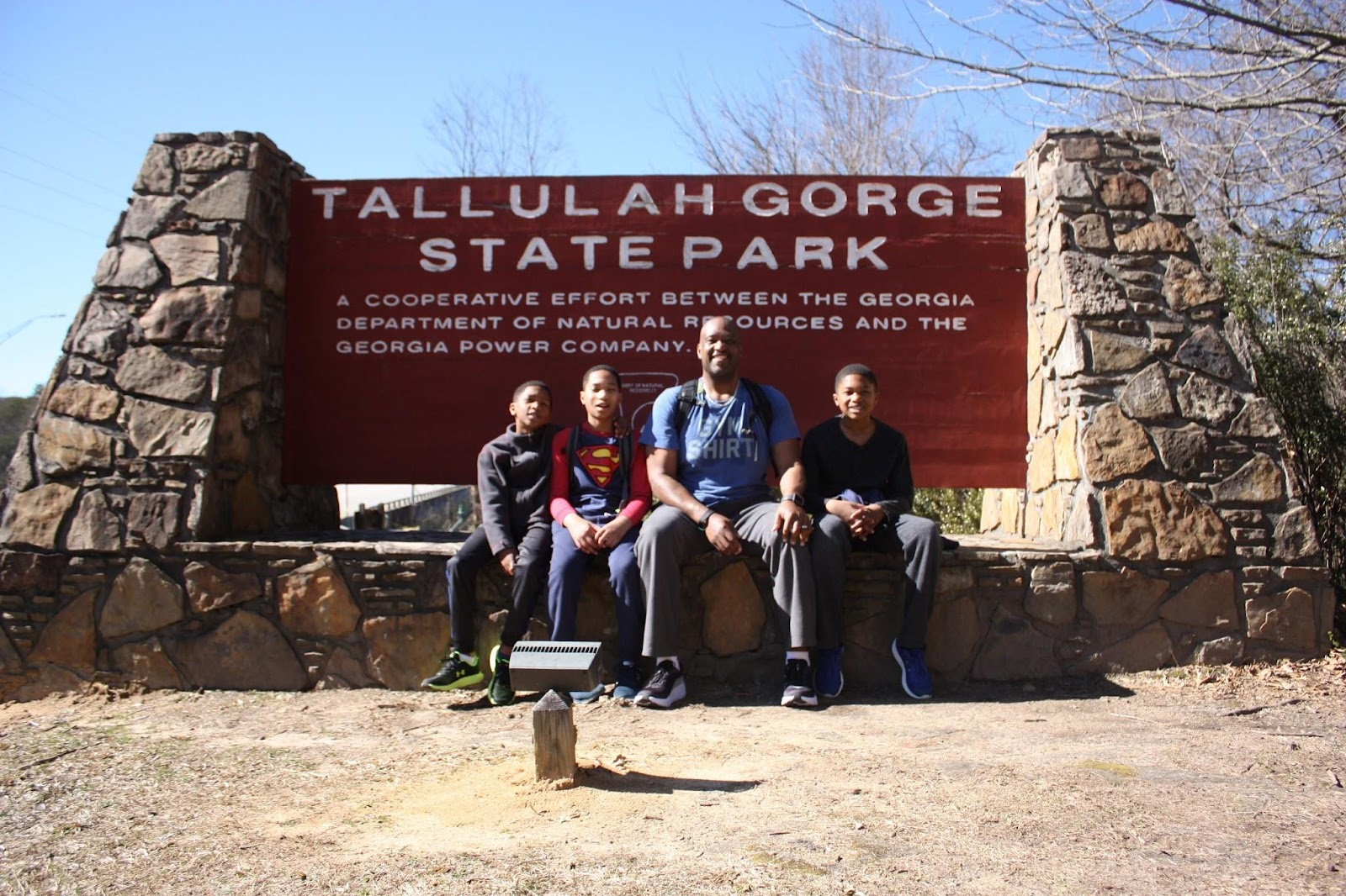 Father and three sons sit in front of a sign for Tallulah Gorge State Park