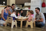 """LePort School Parent & Child Montessori parents gather at the """"weaning table"""" offering their babies snack at school."""