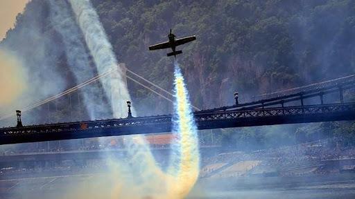 Zoltan Veres, phi công Hungaria, điều khiển máy bay MXS lượn dưới cây cầu cổ nhất của quốc gia này, cầu Lanchid. Vệt khói từ đuôi máy bay để lại đường cong khá đẹp mắt. Ảnh: Getty Images