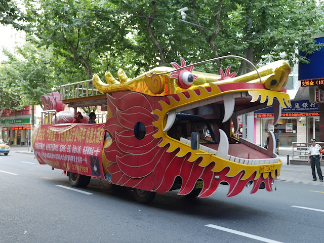 a vehicle (dragonmobile) decorated to look like a dragon driving down a street in Shanghai