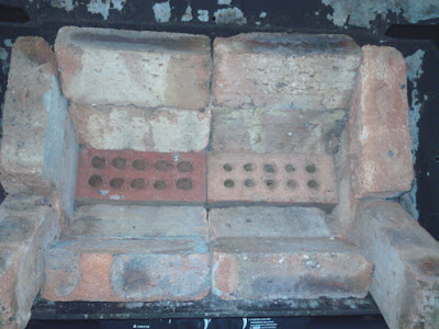 Bricks lining a burnt out gas grill to make a blacksmith forge. The holey bricks on the bottom allow air to come up.