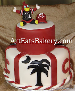 USC Gamecock two tier garnet and black fondant cake with palmetto tree, baseball cap, and cocky figure