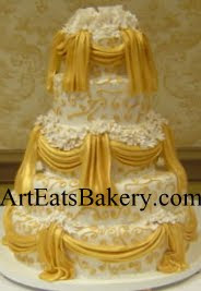 Five tier white fondant wedding cake with hand painted gold drapes, elegant curlicues and edible sugar flowers