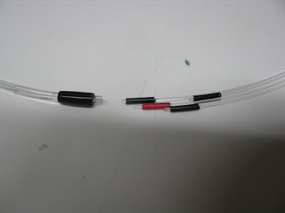 PMMA fibers, left is the polished end, where the miccor is going to be, on the right are the individual fibers with plastic tube over them, coming from an electrical wire. The red is the hot one, the one that brings light into the sensitive area. The black ones are the ones that bring light back to the 3 detectors.