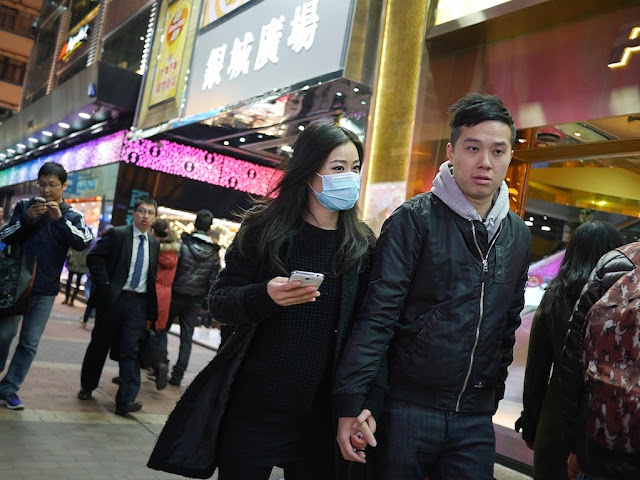 young man holding hands with young woman wearing a medical mask and holding a mobile phone on Sai Yeung Choi Street South