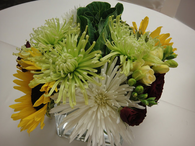 White & green spider mums, sunflowers, spray roses, and freesia
