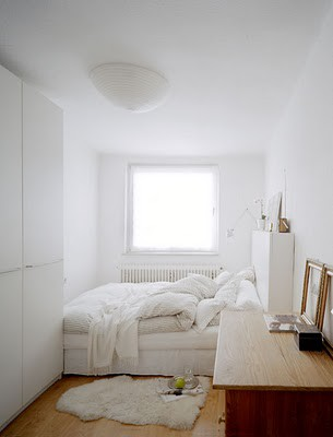the bed in this heavenly white and wood bedroom from small place style takes up the entire far end of the room fitting perfectly between the three walls
