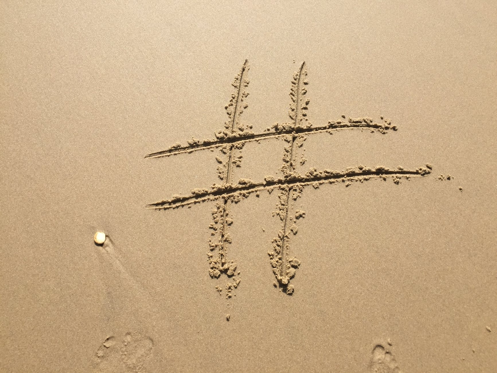 image showing hashtag written in the sand