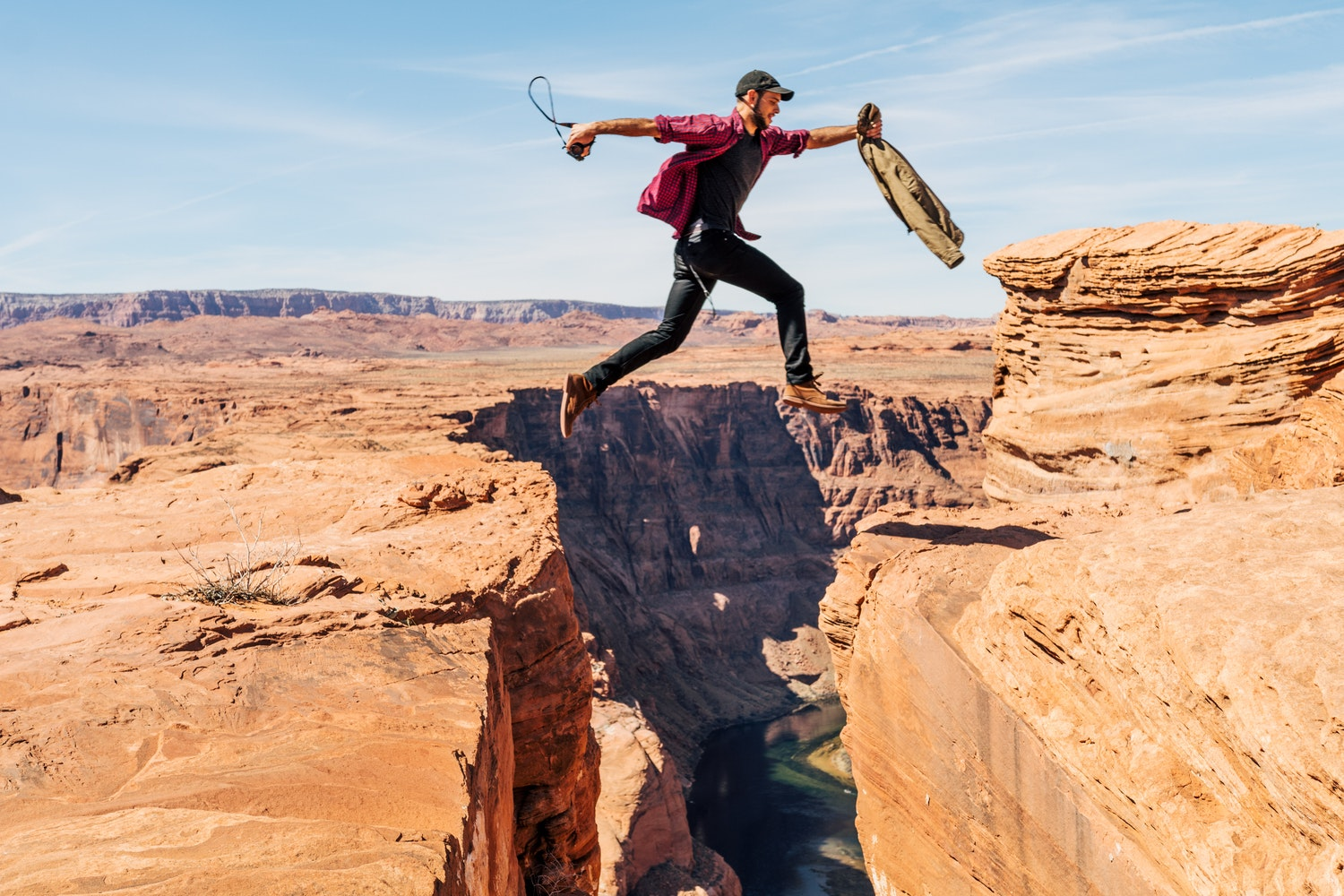 Image of a guy is jumping two peaces of mountains