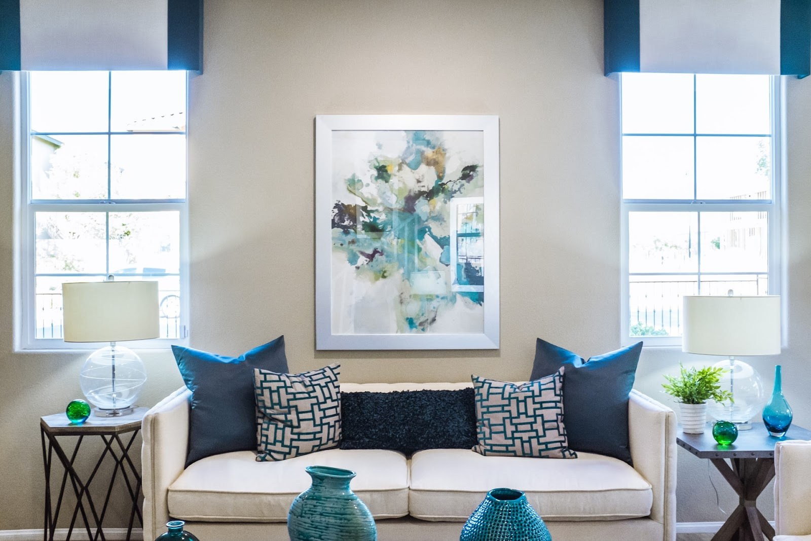 living room done in a tasteful colour combination of white and blue with a sofa and a picture hanging on the wall