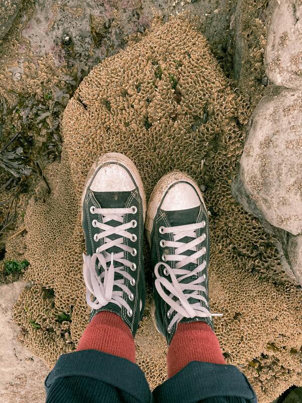 Foto dos pés usando um all star desgastado, meias vermelhas e calça de veludo com as barras dobradas.