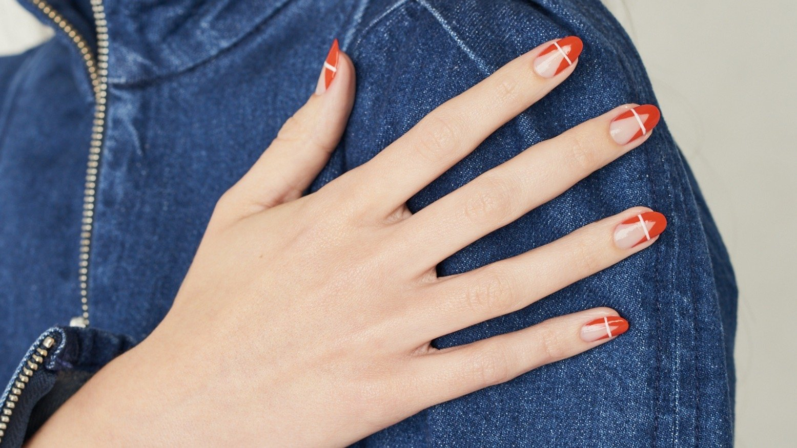 Negative space manicure with red tips & sides at the top & gold stripe across the middle top