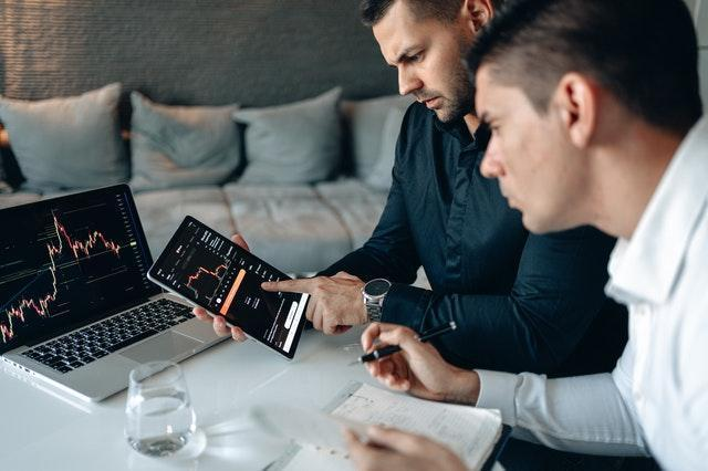 Two men looking at graphs on a tablet and a laptop