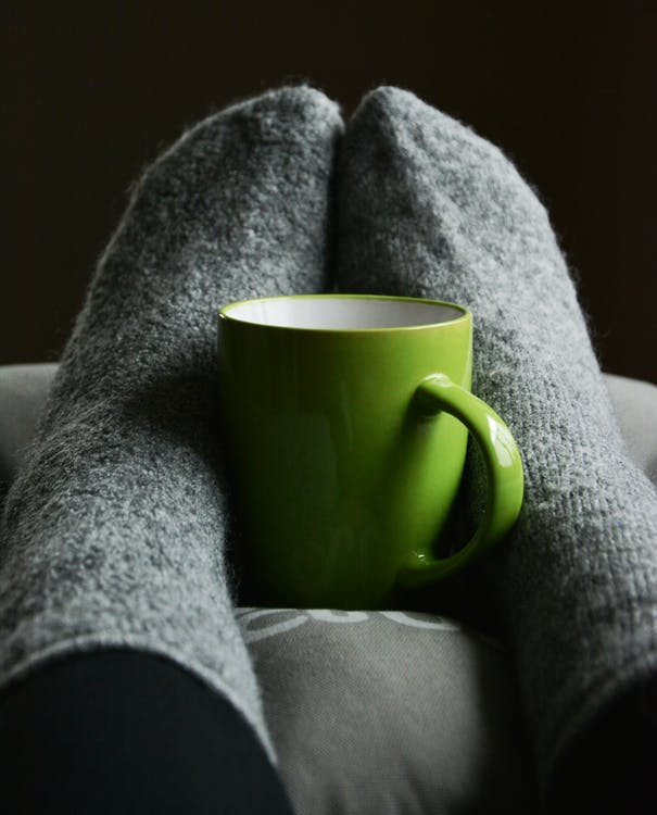 Green Ceramic Mug on Person's Feet