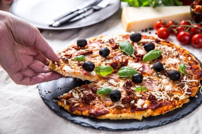 Obraz zawierający pizza, żywność, osoba, talerzOpis wygenerowany automatycznie