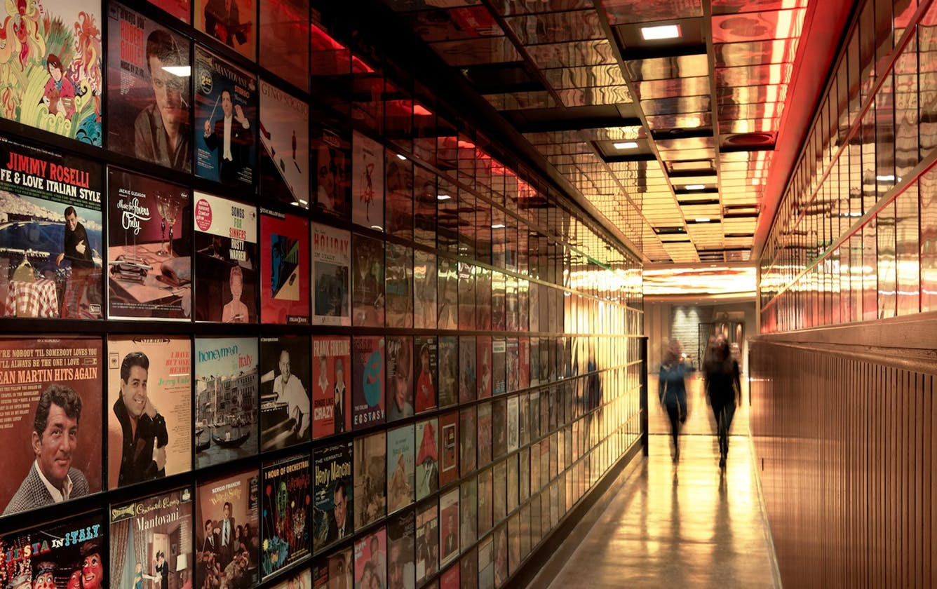 The scene at Secret Pizza inside the Cosmopolitan hotel in Las Vegas with two women walking down a hallway covered in famous album artwork and vinyl records.
