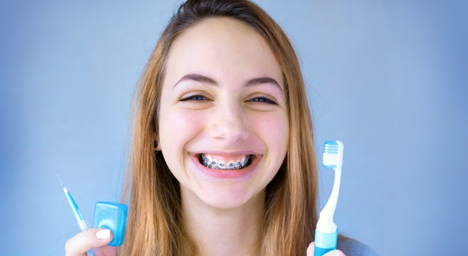 Young girl smiling with toothbrush and floss