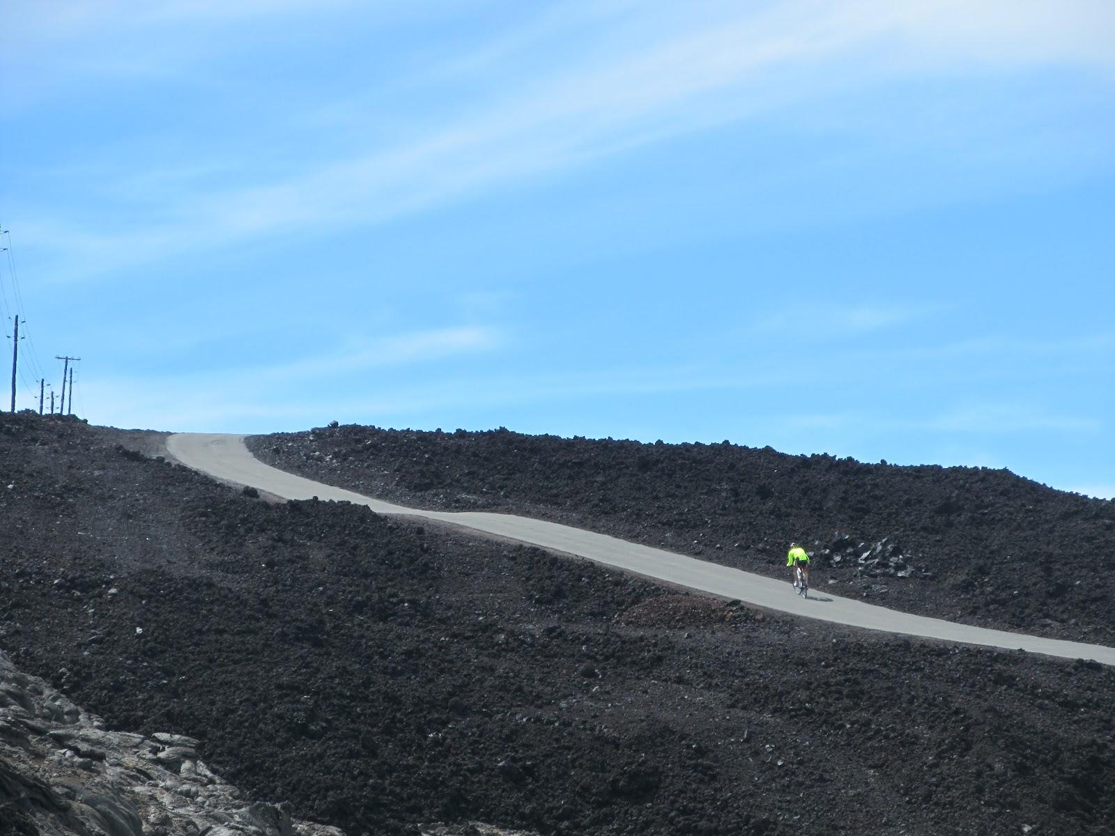 Climbing by bike Mauna Loa Volcano - cyclist climbing steep section of Mauna Loa Observatory Road