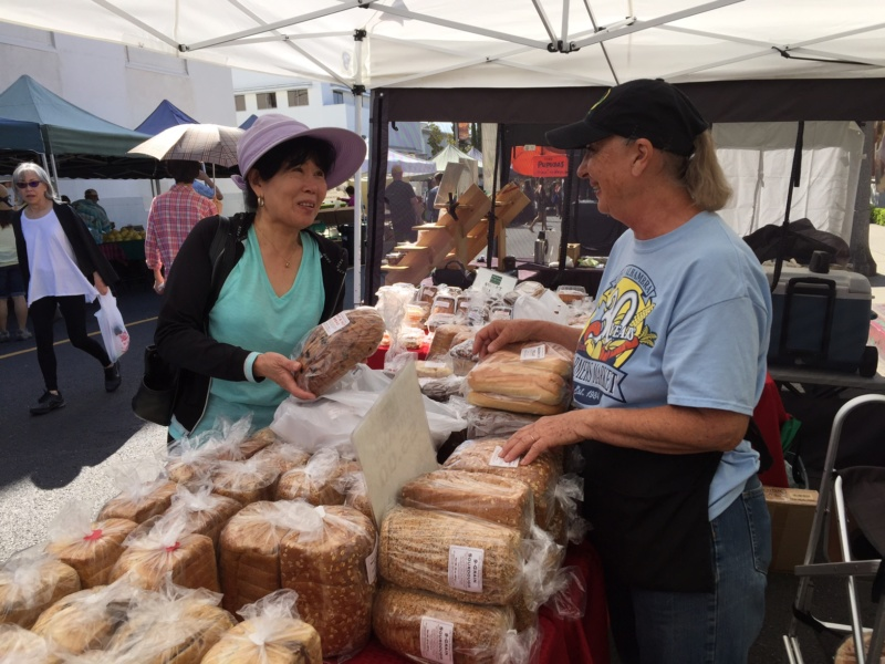 Vendor selling bread to a patron at a farmers market booth