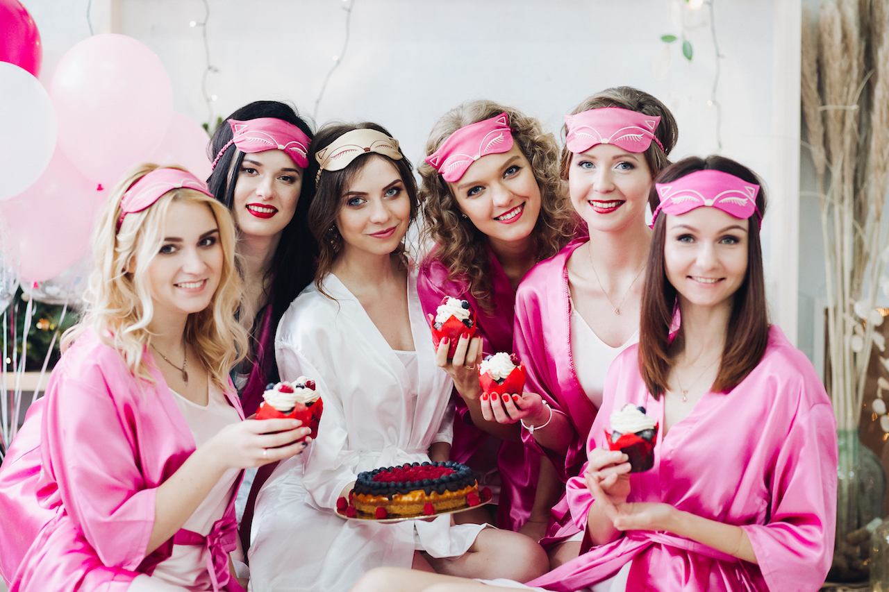 girls dressed up at bridal shower eating cupcakes