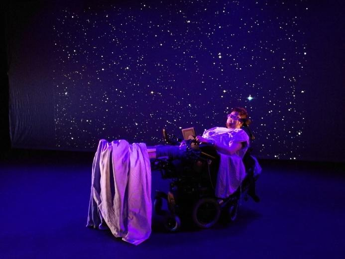Image description: Artist Jamie Hale is reclined in their powered wheelchair with legs elevated. Jamie has hospital bedsheets over them, and is on a dimly lit stage with a starry night backdrop.