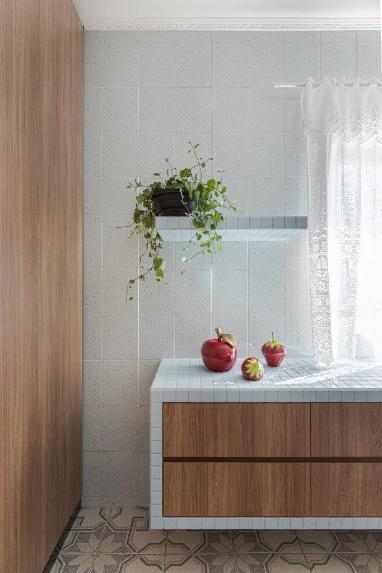 Cozinha com armário de madeira e superfície revestida de pastilhas brancas.