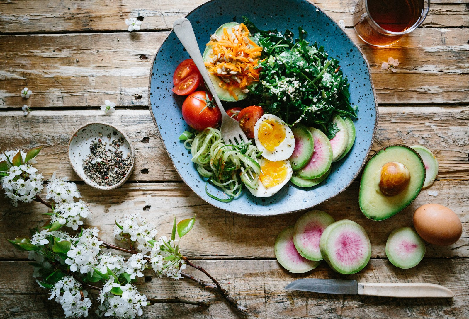 Avocado, egg, and tomato salad dish on a table with leftover ingredients on the side.
