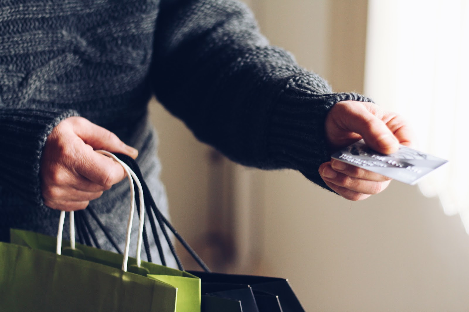 Um homem entregando um cartão para alguém, enquanto segura sacolas de presentes.